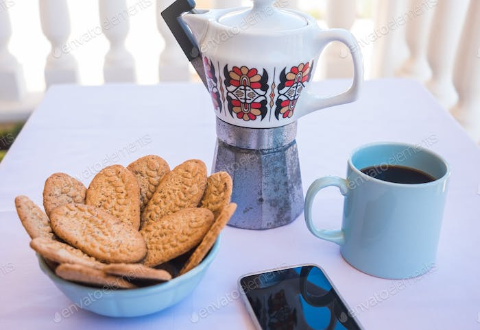 Breakfast or break outdoor on the balcony with coffe cup and whole grain biscuits