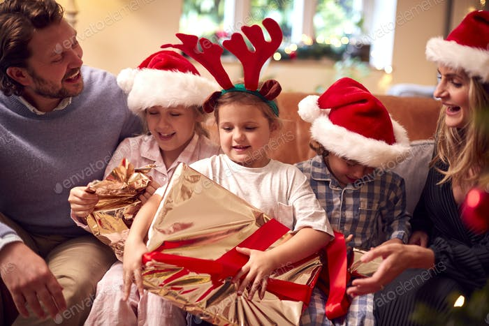 Family Wearing Santa Hats Sitting On Sofa At Home Opening Christmas Gifts