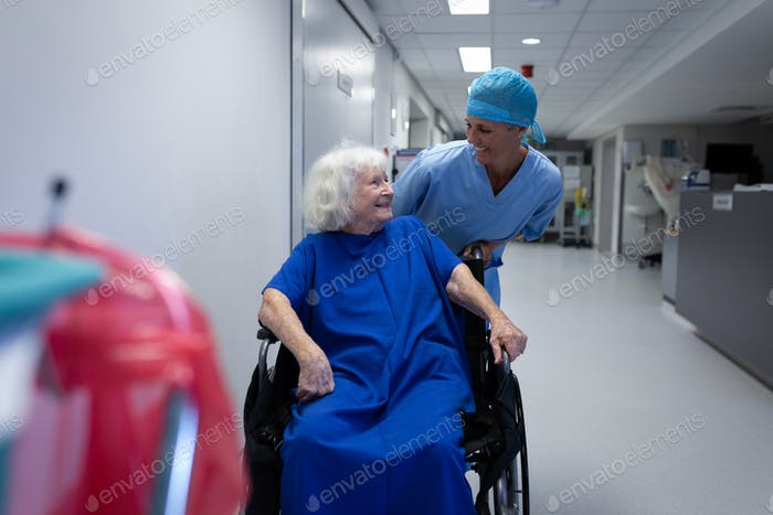 Female surgeon talking with senior female patient sitting in a wheelchair in hospital corridor