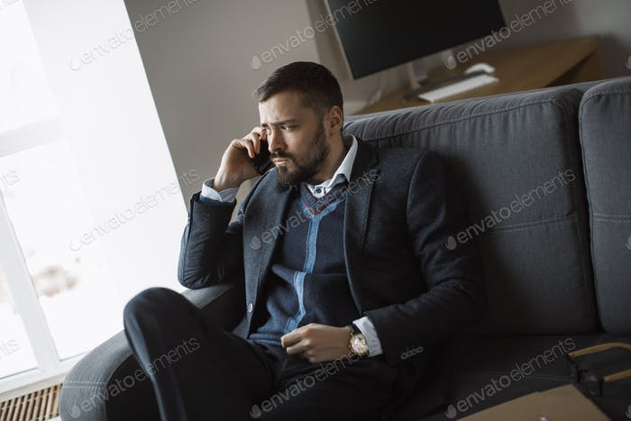 Serious Man in Talking on Smartphone