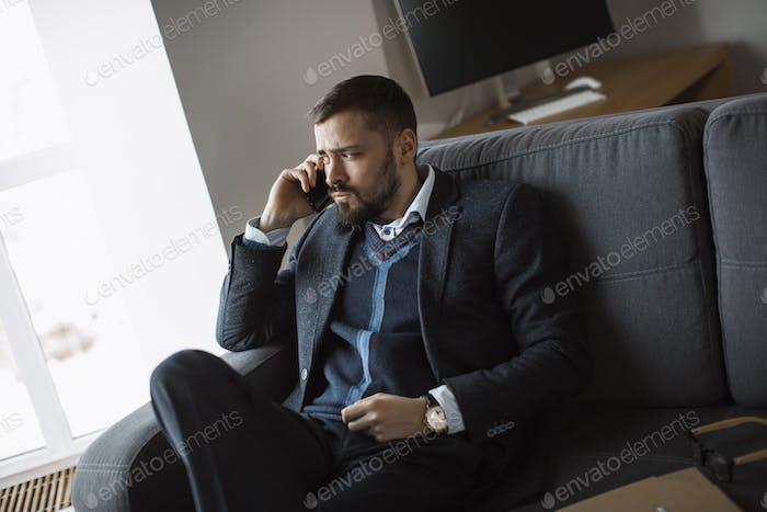 Hombre serio en hablar en el teléfono inteligente