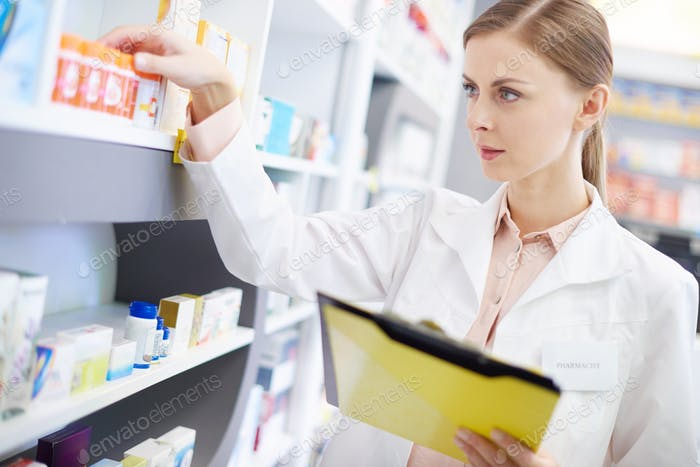 Young pharmacist looking at shelf of pills