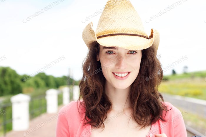 Smiling young woman standing in cowboy hat outside