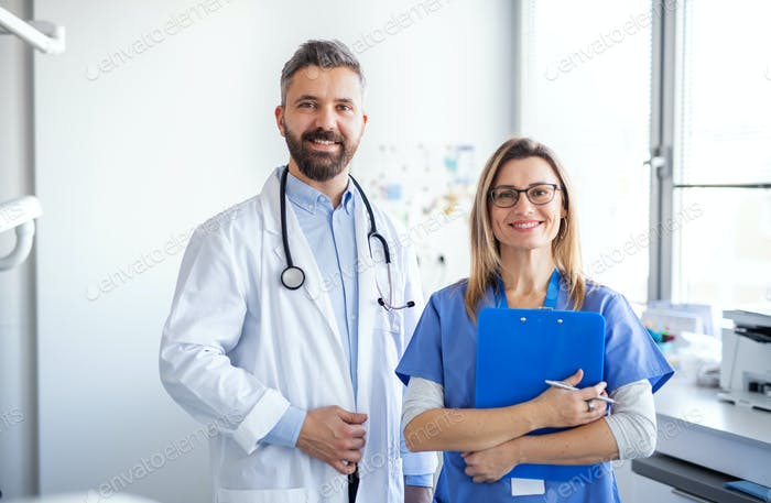 A dentist with dental assistant in modern dental surgery, looking at camera