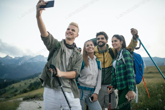 Travel, tourism, hike and people concept - happy group of friends taking selfie and hiking