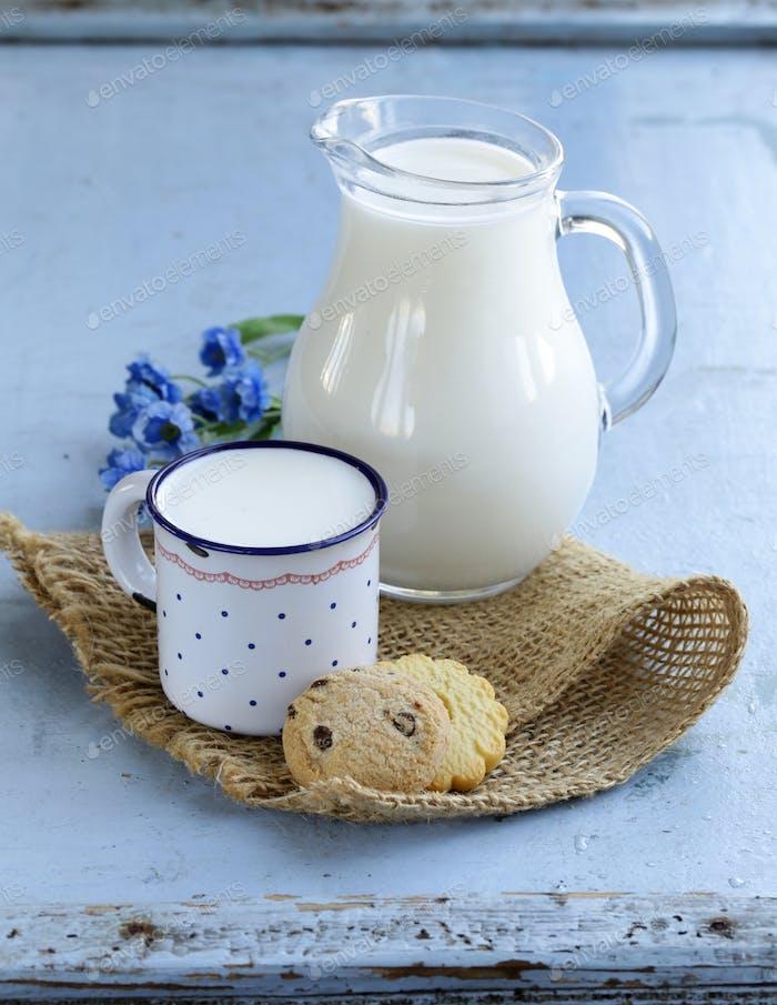 Krug mit Milch auf Holztisch