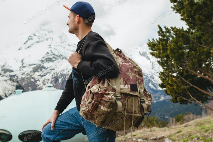 young hipster man sitting in mountains