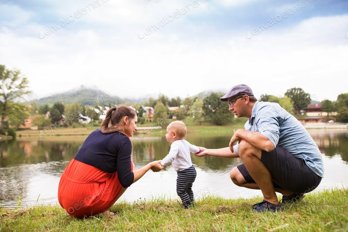 Little boy with parents making first steps.