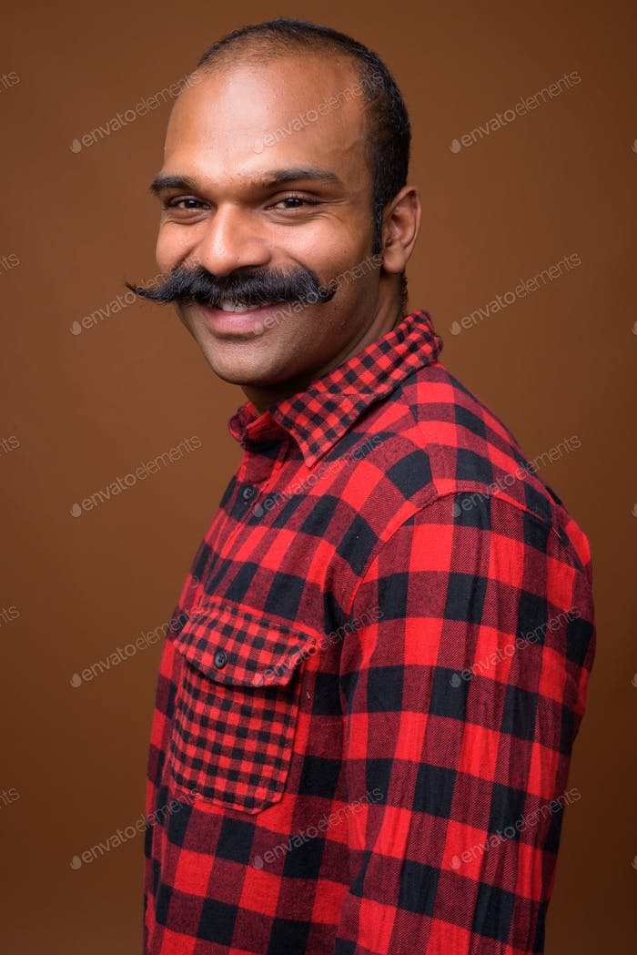 Portrait of happy Indian hipster man with mustache