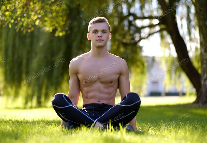 Shirtless fitness male doing yoga in a park.