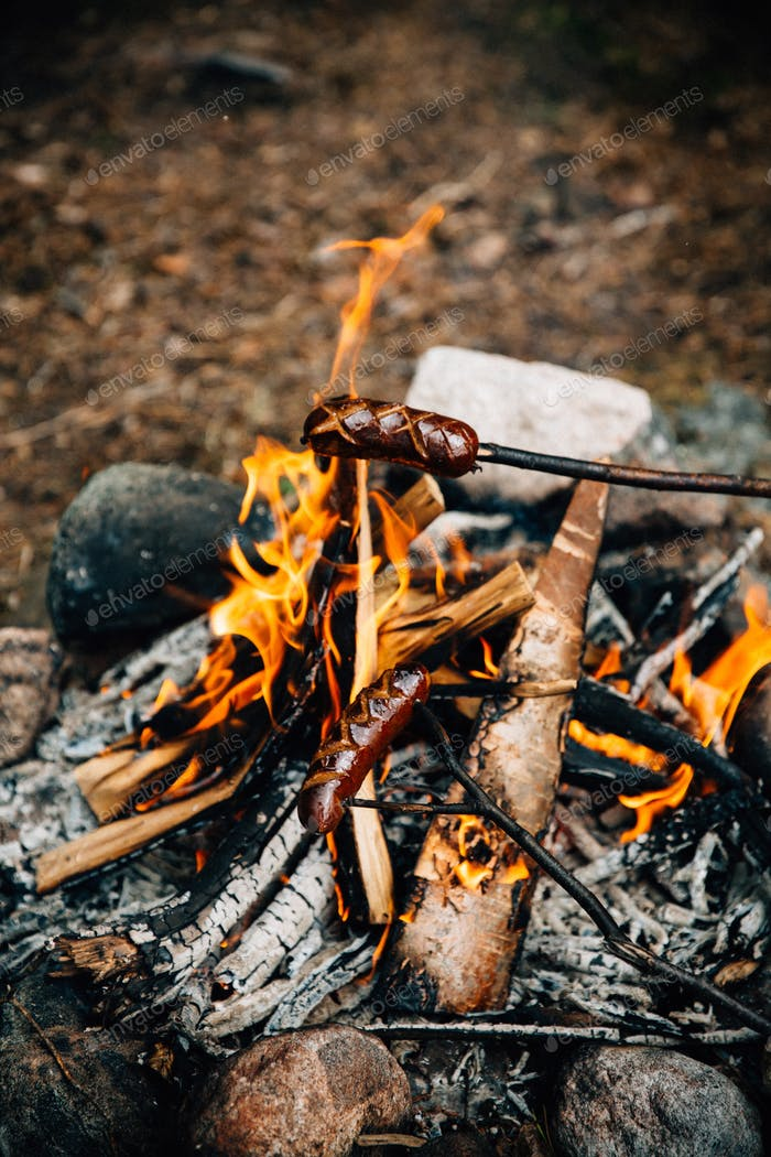 Grilled sausages above the campfire