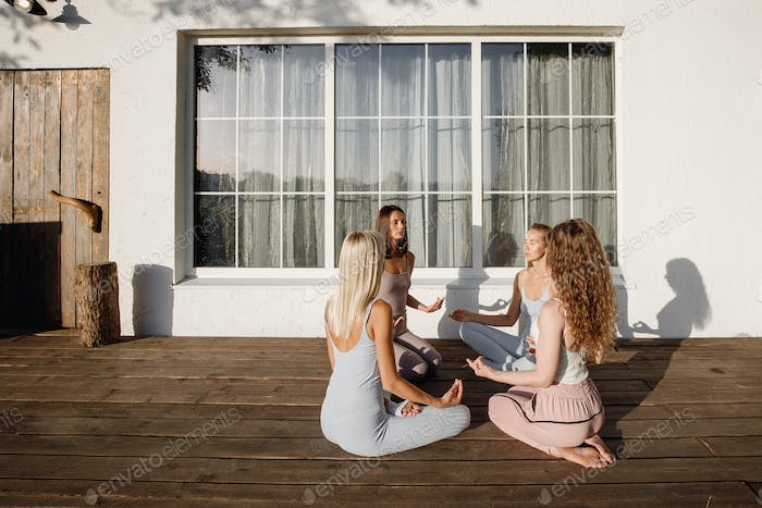 Four young girls are sitting with closed eyes in a circle on a wooden podium in the garden in the