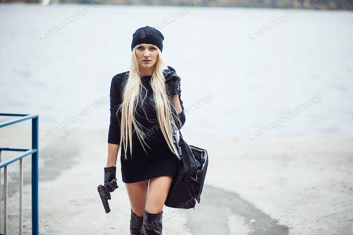 Sexy blonde Mädchen mit Waffe