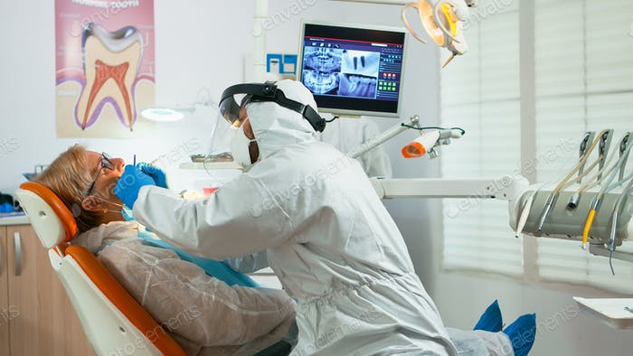 Orthodontist in protective suit lighting the lamp until examination