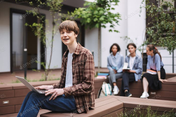 Photo of smiling boy sitting on bench with laptop on knees and joyfully looking in camera