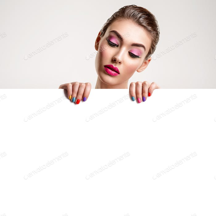 Beautiful  woman with a colored manicure holds blank poster.