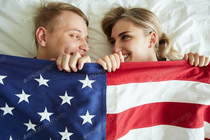 Glückliche junge Dates bedeckt mit amerikanischer Flagge beim Liegen auf dem Bett