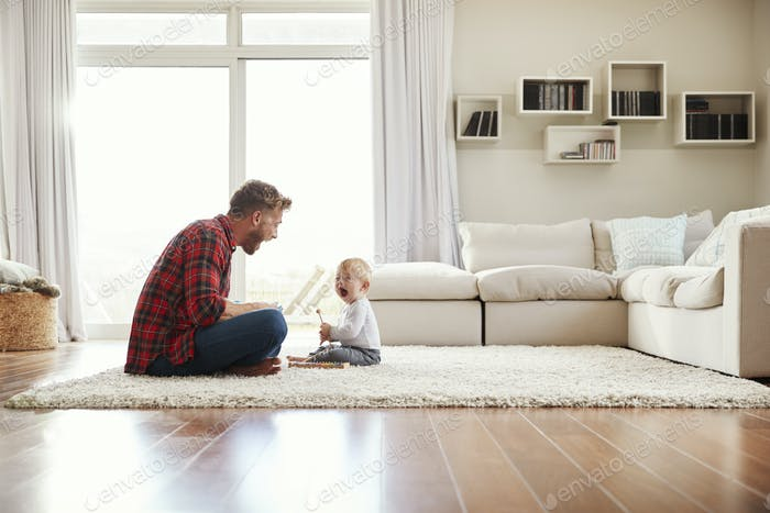 Young father and son playing together in their sitting room