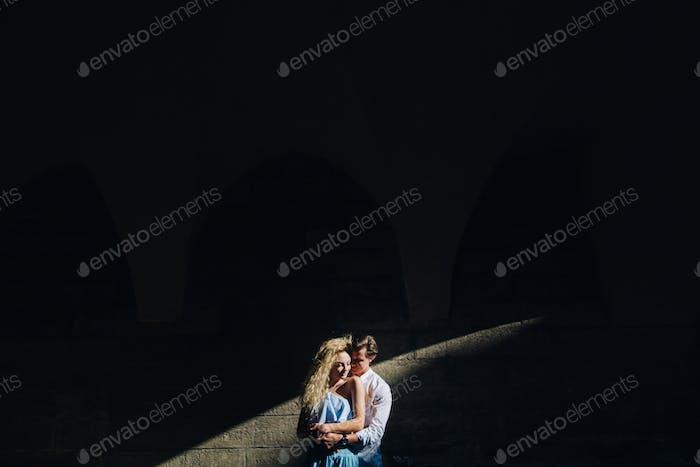 Счастливая пара обнимает возле стены