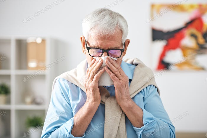 Sick senior retired man with handkerchief by his nose staying at home