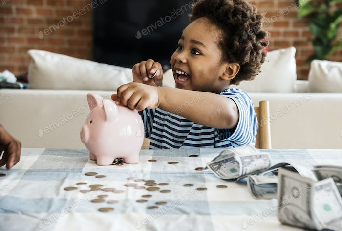 Black boy collecting money to piggy bank