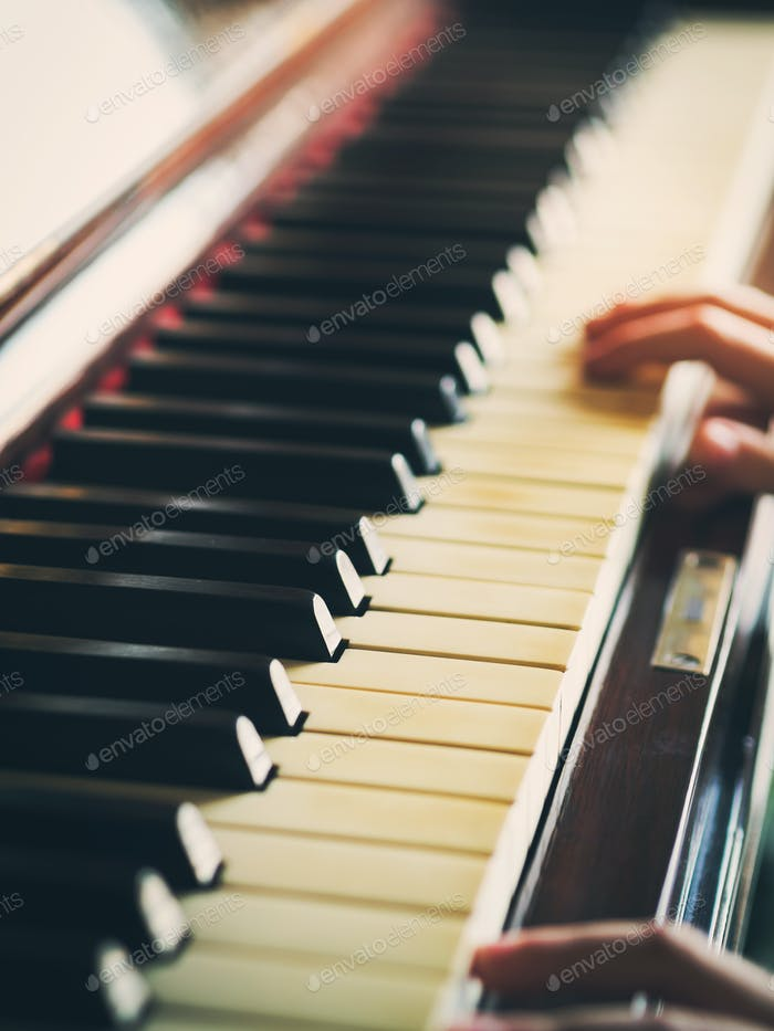 Vintage piano keys and hands playing