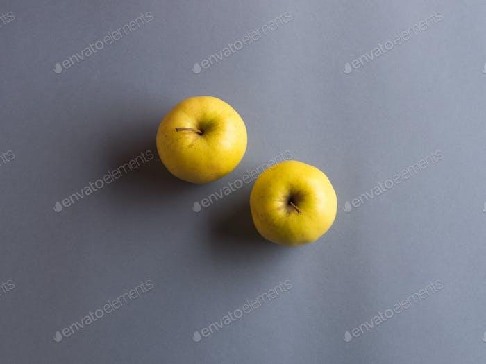 Beleuchtete gelbe Äpfel auf dunkelgrauem Hintergrund
