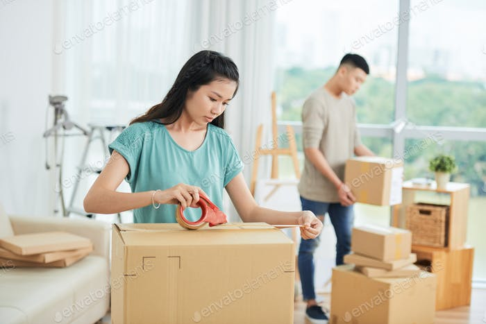 Couple packing the boxes to move