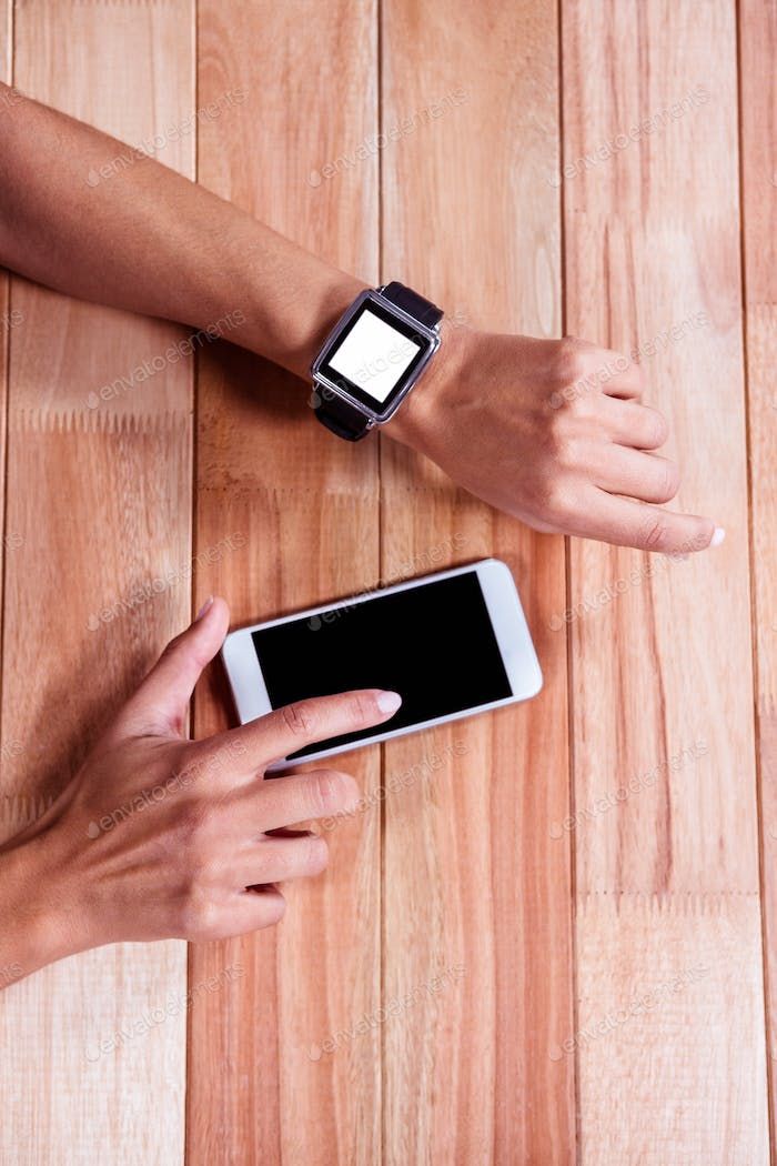Woman with smartwatch using smartphone against wooden plank