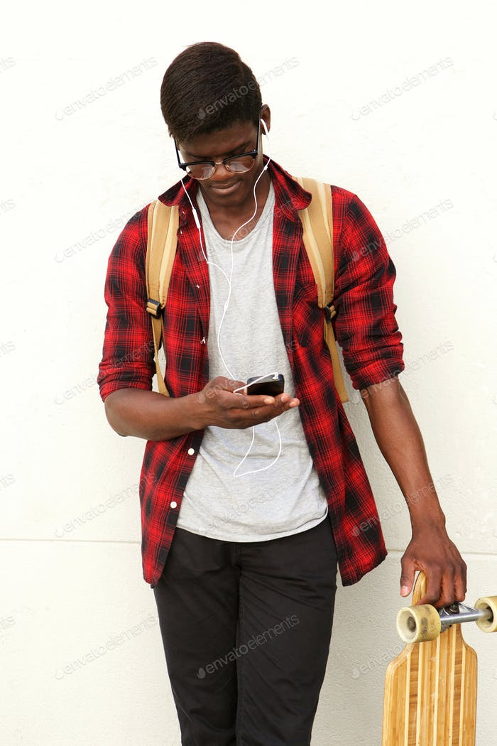young african male student standing against white wall with mobile phone and skateboard