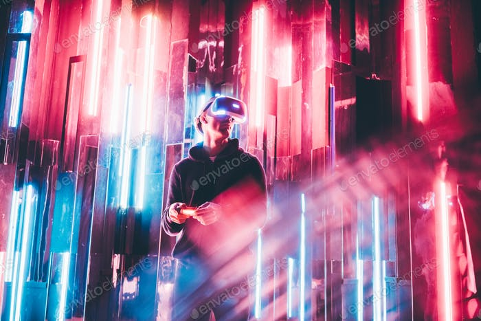 Man using VR headset in dark interior illuminated neon light.
