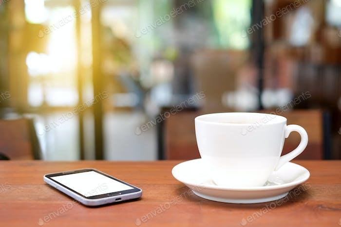 Weiße Kaffeetasse und Smartphone auf Holztisch mit verschwommenem ca