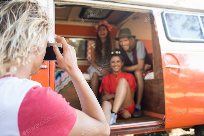 Mann fotografiert glückliche Freunde sitzen im Wohnmobil