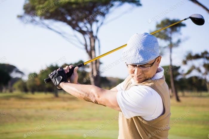 Half length of sportsman playing golf