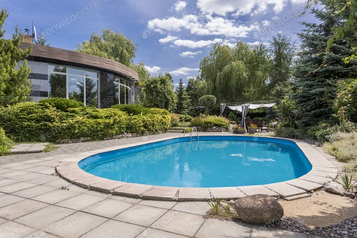 Oval swimming pool in big garden