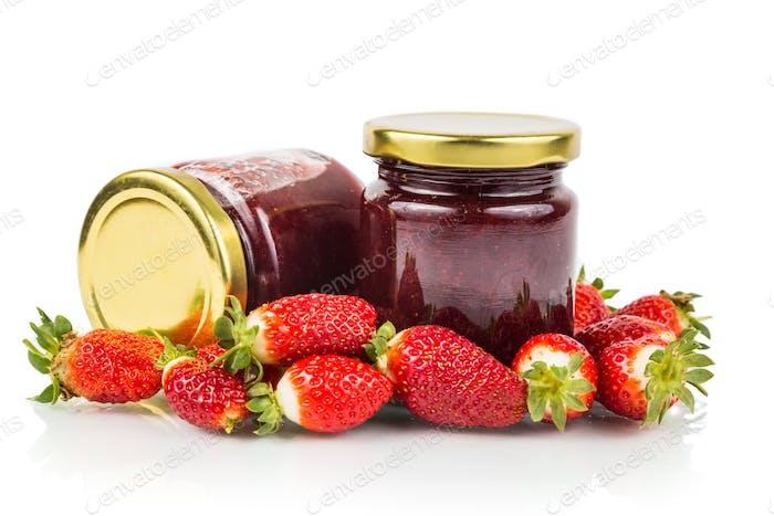 Organic strawberry jam in transparent glass jar with fresh straw