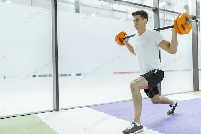 Handsome man exercising and lifting weights