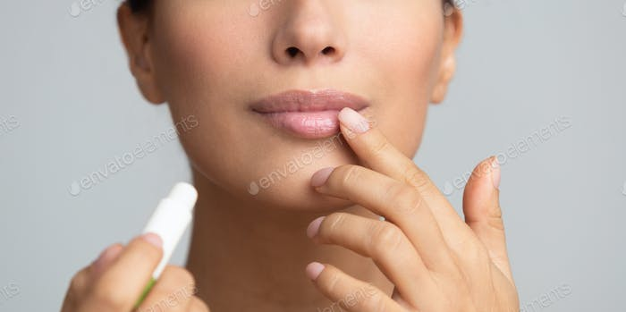 Lips skin care. Afro woman applying balsam