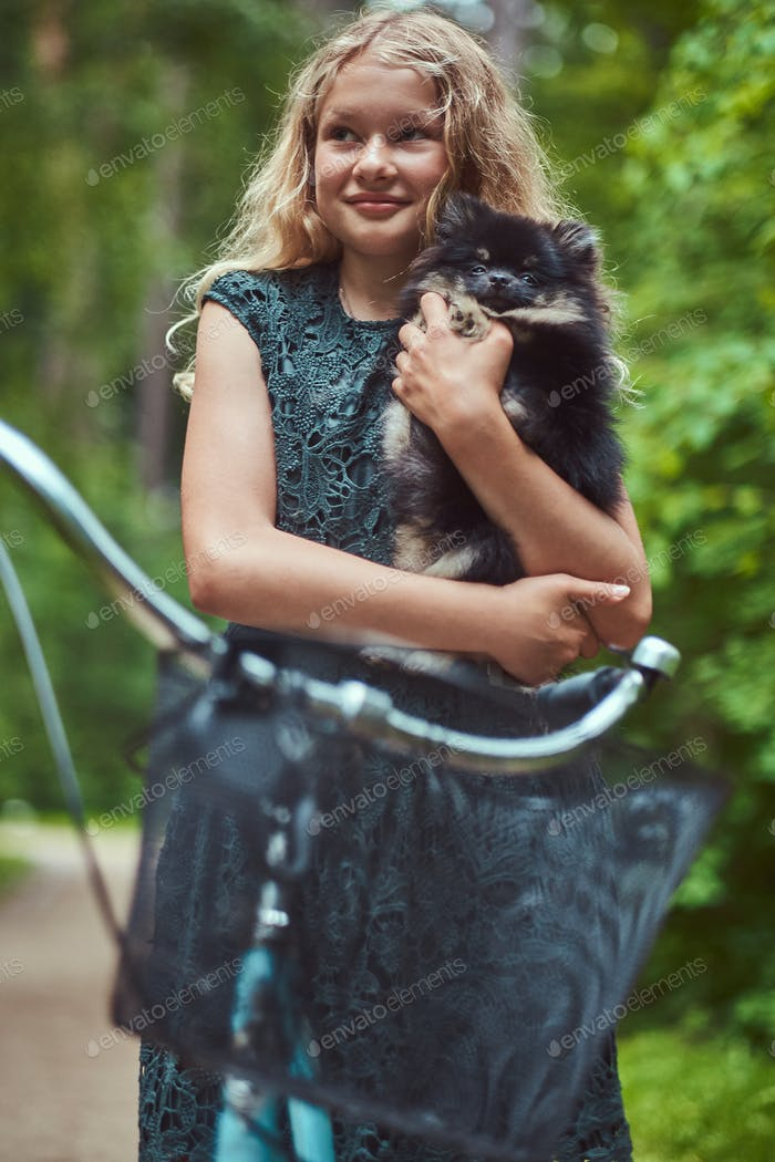 Portrait of a little blonde girl in a casual dress, holds cute spitz dog, in a park.