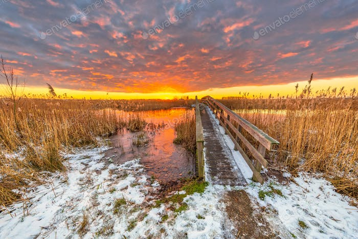 Winter landscape pathway over wooden bridge under orange sunset