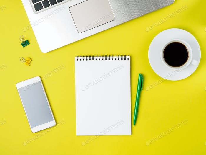 Top view of modern bright yellow office desktop