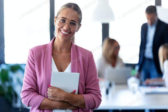 Smart young businesswoman looking at camera while holding her digital tablet on coworking place.