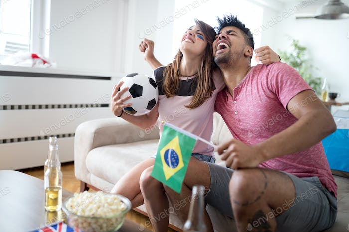 Young couple sport fans watching match on television