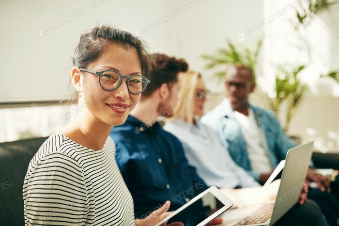 Smiling young Asian businesswoman sitting with coworkers in an office