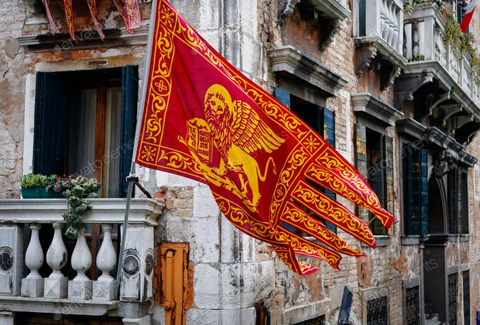 Colors of Venezia, golden-red flag, old building at background