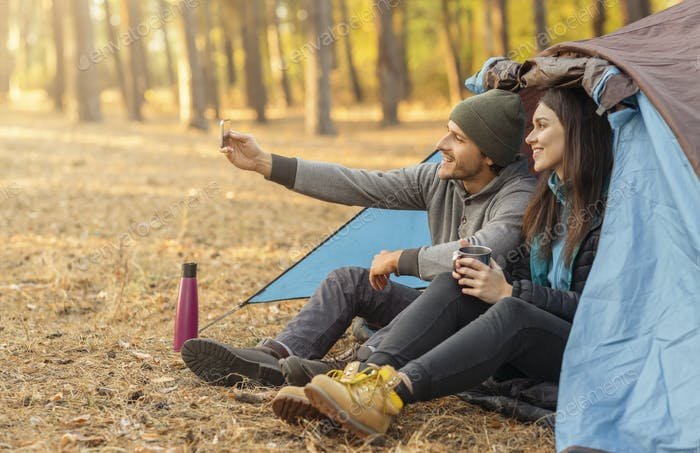 Couple of tourists taking selfie in camping tent