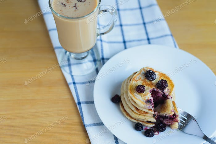 eating of fritter or oladyi with bramble with fork on white plate and cappuccino