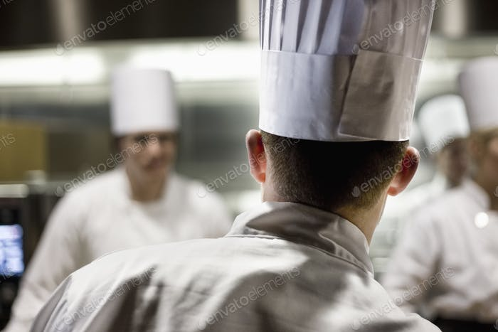 A closeup view from behind of a chef  wearing a toque hat in a commercial kitchen.