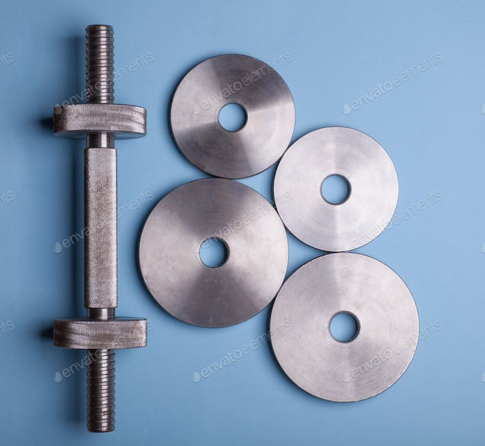 dumbbell with weights isolated on blue background