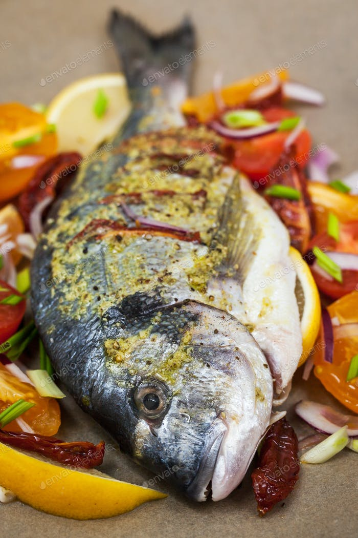 Raw whole sea bream fish and vegetables
